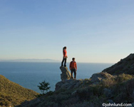An Hispanic couple is up on a cliff overlooking the ocean and just watching.  The girl is standing on a rock outcropping that makes her above her boyfriend. Beautiful scenic picture of a couple watching the ocean.